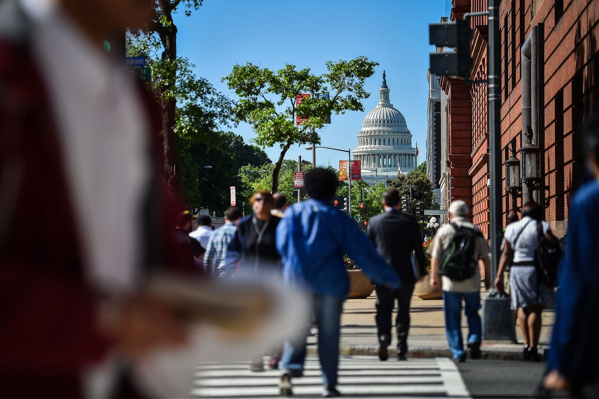 Pedestrians cross a street in view of a domed capital building.