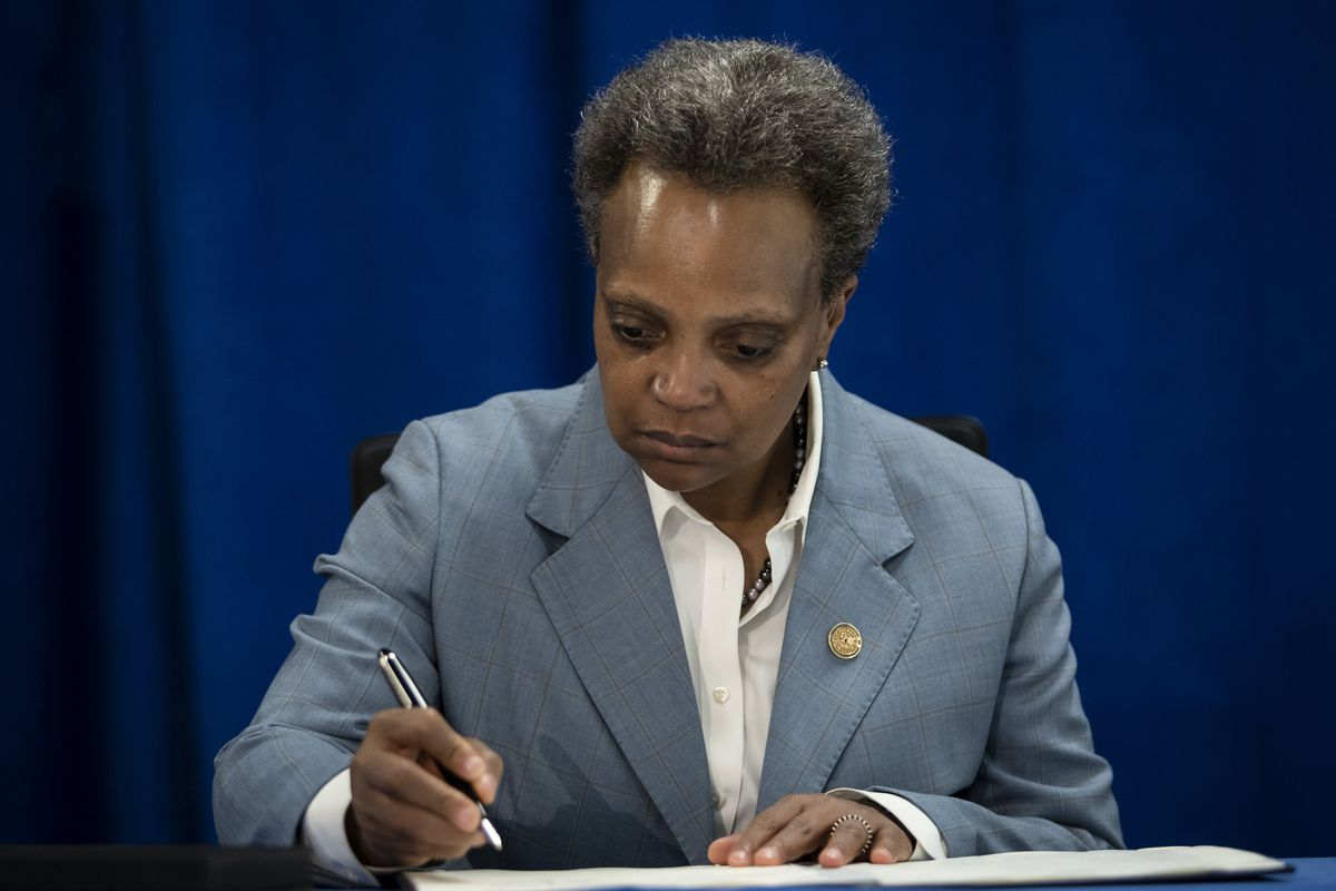 Mayor Lori Lightfoot signs an executive order Tuesday to ensure coronavirus-related benefits offered by the city of Chicago are available to immigrants and refugees.