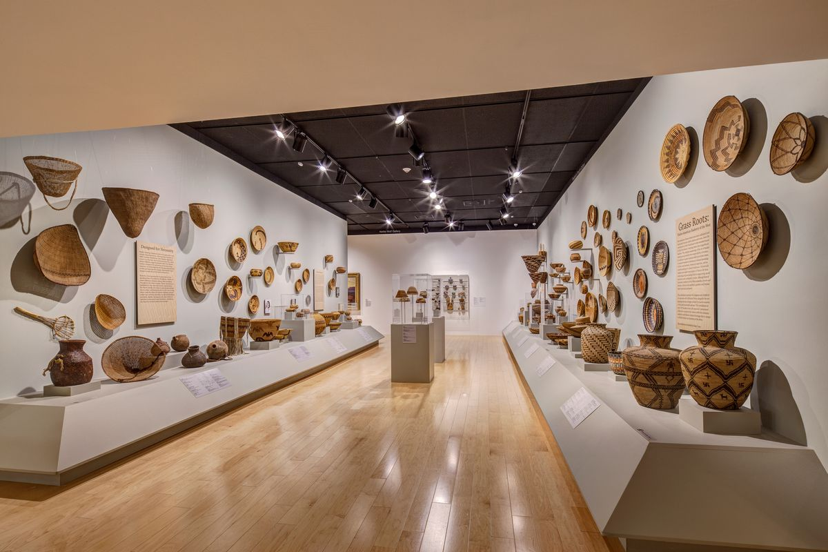 The interior of a museum with many items and objects on display on shelves and on the wall.