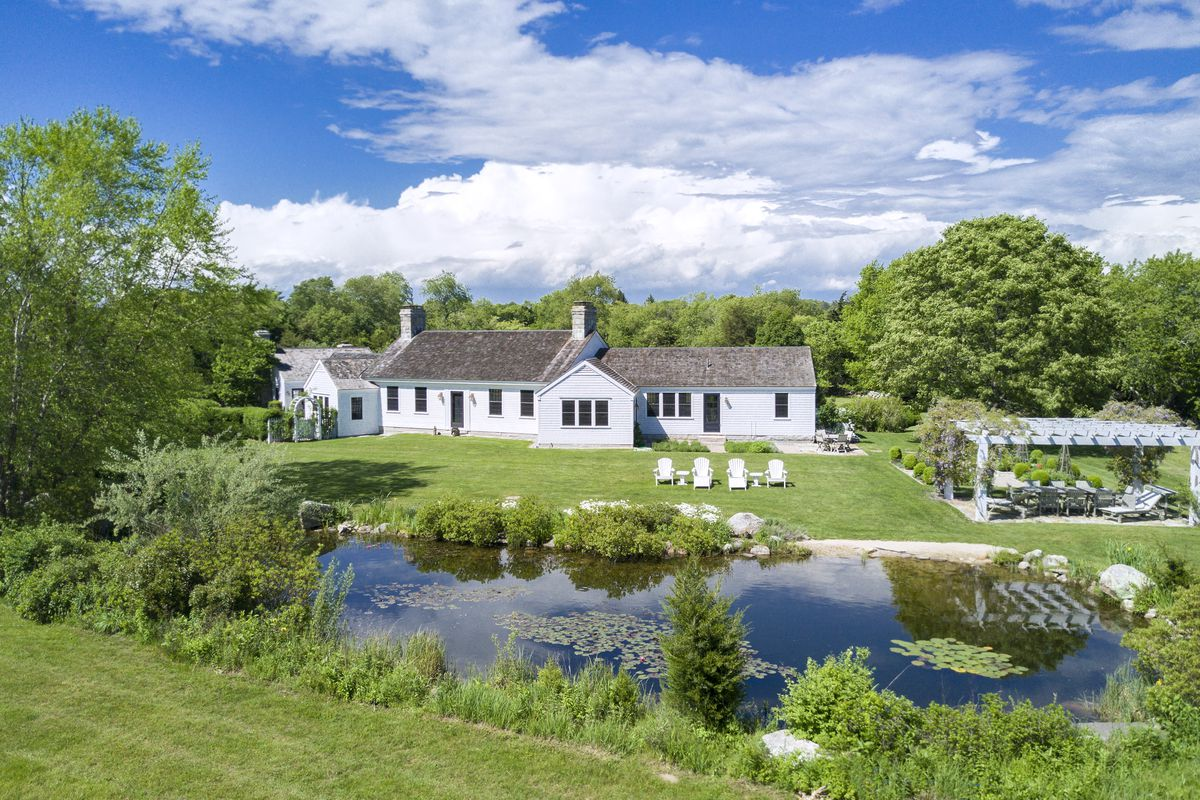 A white clapboard house with shingle roof sits on a grassy yard in front of a pond.