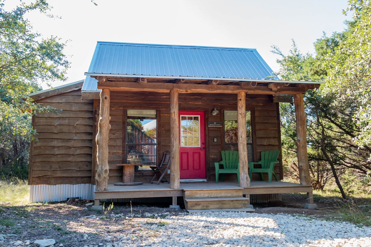 A cabin with dark brown wood panels with a patio lines with brown tree trunk columns and green patio chairs and a red door and two windows