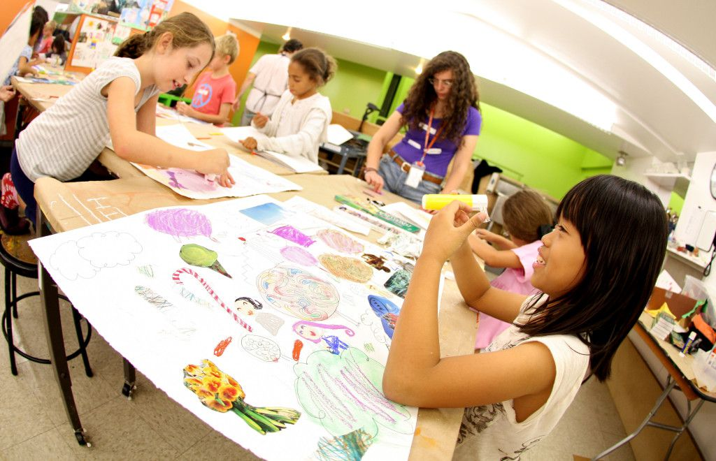 A group of children sit around a large table with various arts and crafts materials on the table.