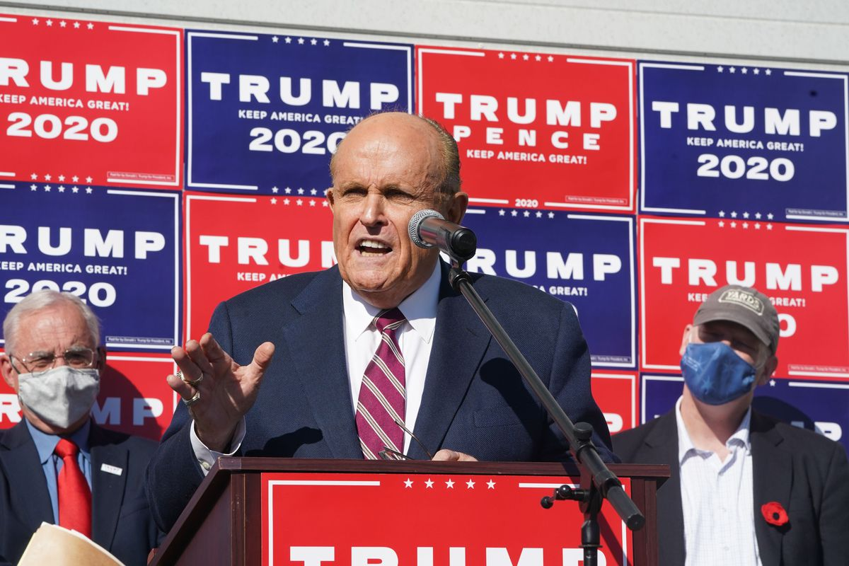 """Giuliani, in a dark suit and red tie with white stripes, speaks under a bright sun. He is behind a podium, and behind him are alternating red and blue signs that say """"Trump 2020"""" in white."""