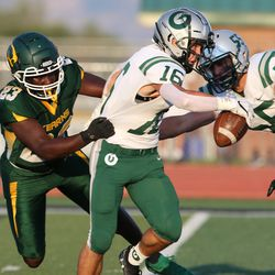 Olympus' Peyton Rice (16) is brought down by Kearns' Tray Swanigan (23) during a high school football game at Kearns High School in Kearns on Friday, Aug. 28, 2020.