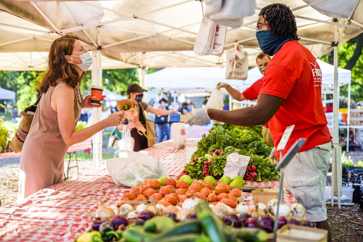 A farmers market vendor talks with a cheery customer. They are both wearing masks.
