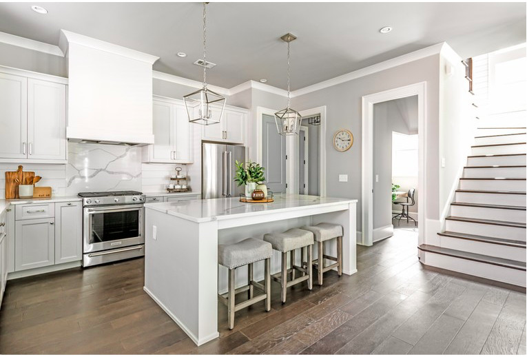 A white kitchen with wood floors and a staircase in white at right.