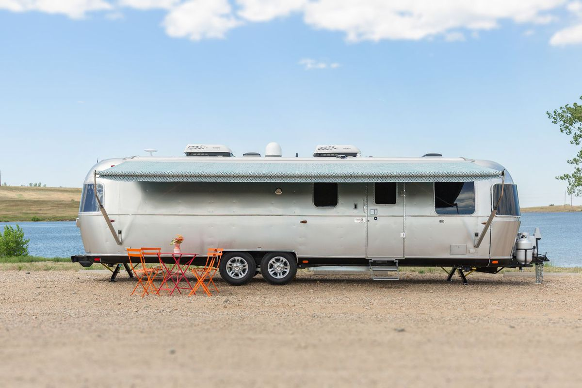 An exterior view of a silver Airstream travel trailer that has an awning out and an orange dining set in front.