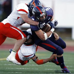 Woods Cross' Sean Barton, right, is tackled by Mountain Crest's Troy Netzley, down, and Stetson Weston on Friday.