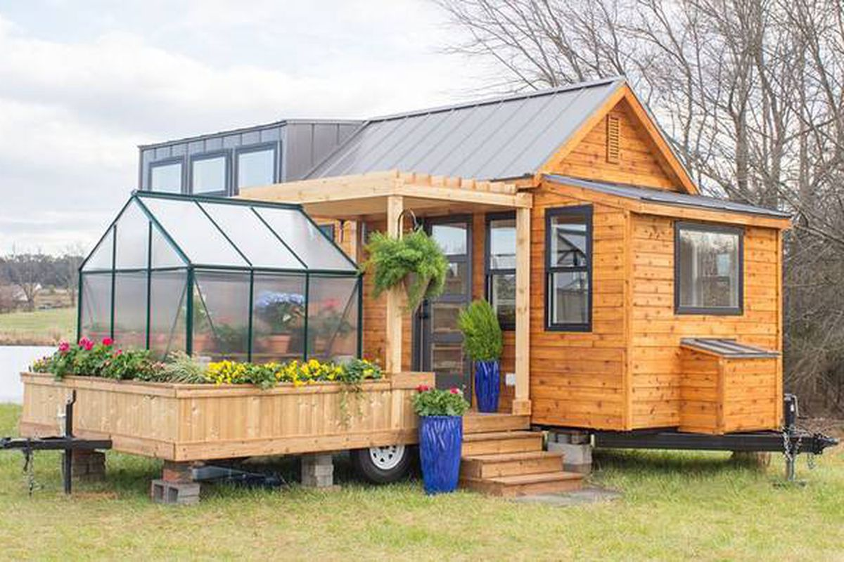 tiny house comes with a greenhouse and porch