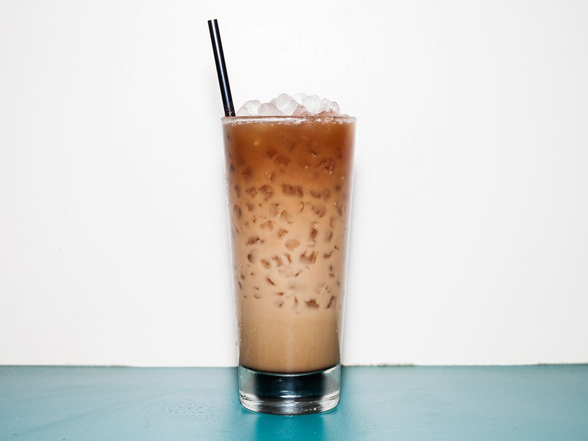 A tall cocktail made with coffee, milk, and lots of ice stands against a white backdrop.