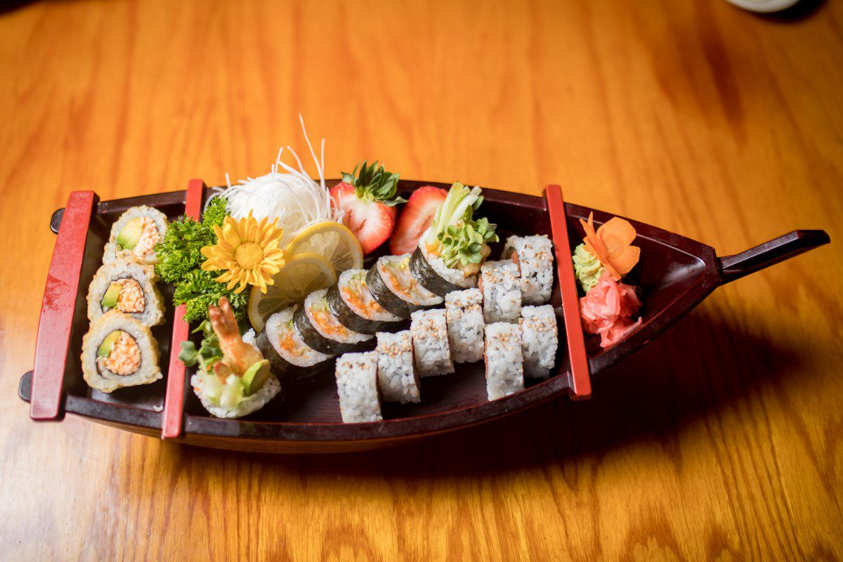A wooden boat with pieces of sushi rolls on it.