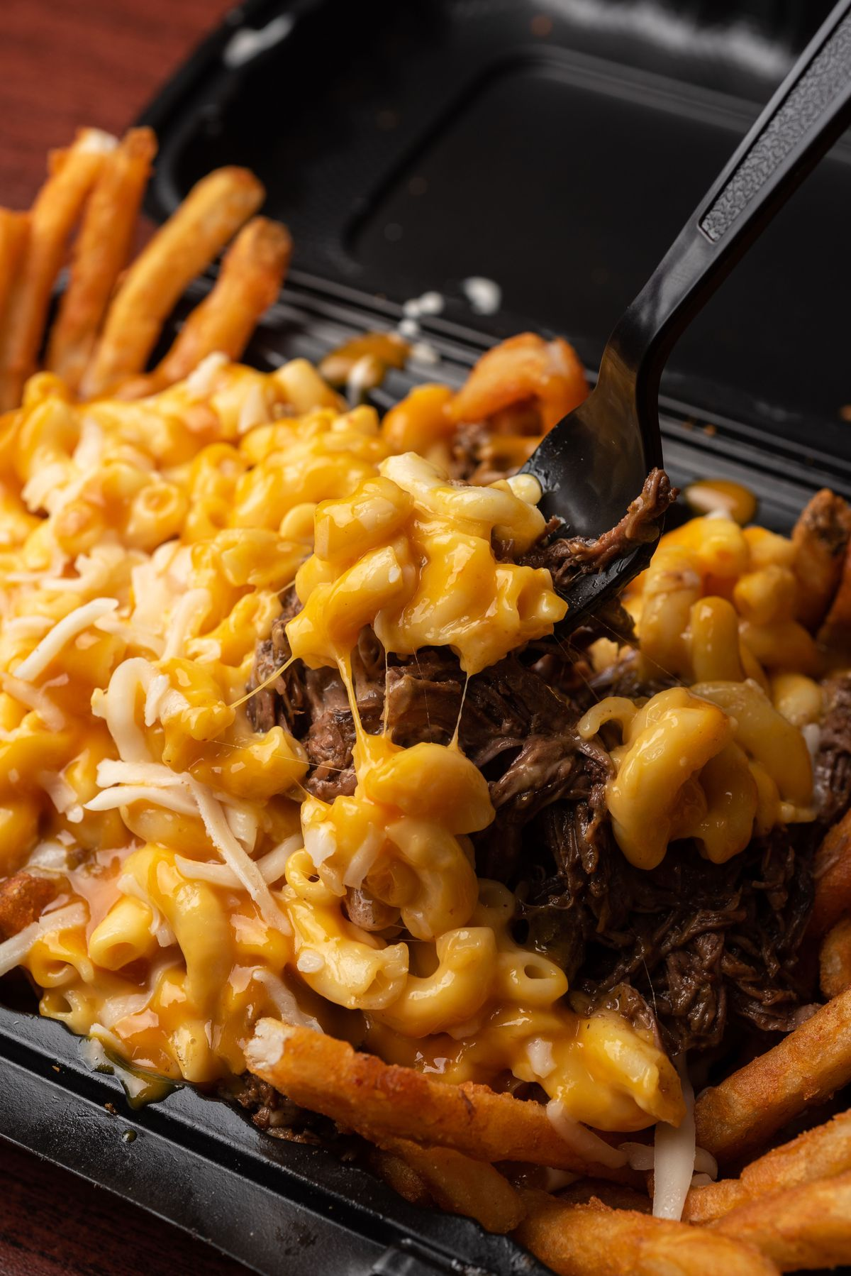 Mac and cheese over brisket and french fries in a styrofoam container.