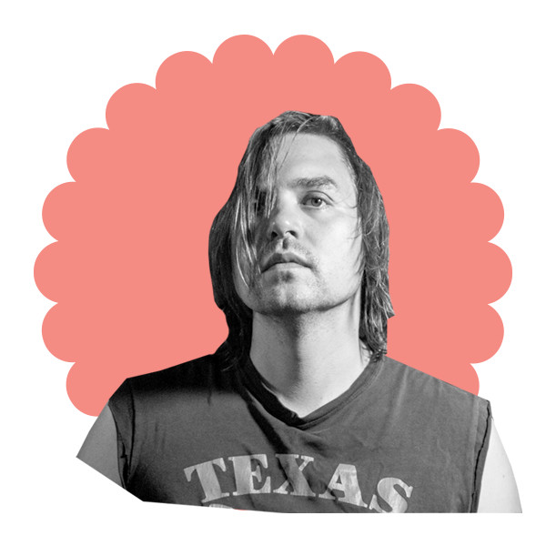 """A black and white image of Will Butler with straight, chin-length hair, wearing a t-shirt that reads """"Texas"""" on the front and has the sleeves cut off."""