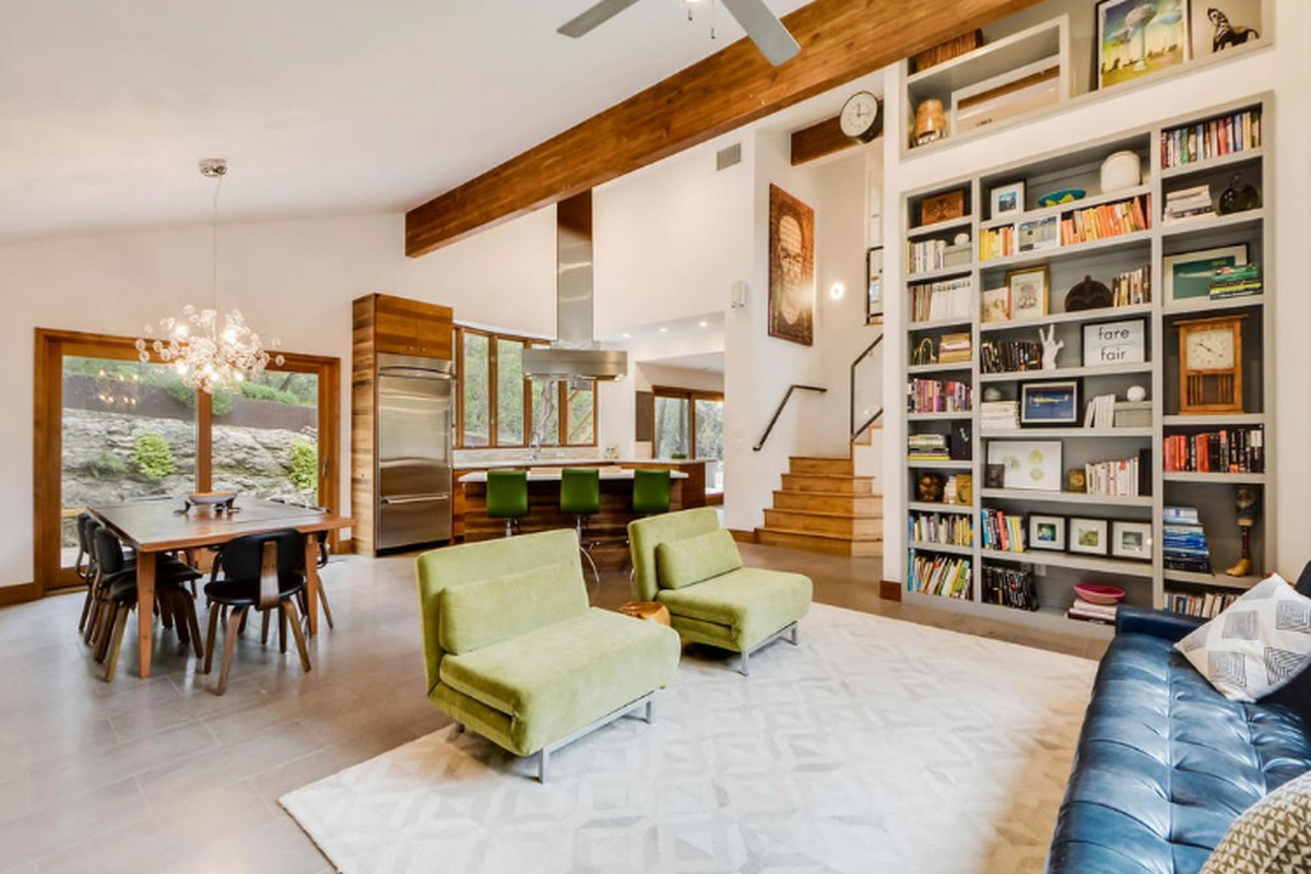 Large living area with vaulted, beamed ceiling, built-in floor-to-ceiling shelves, open kitchen, sliding glass doors