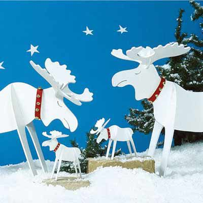 Two big reindeers and two baby reindeers lined up in a wooden outdoor Christmas decoration in front of evergreen trees.