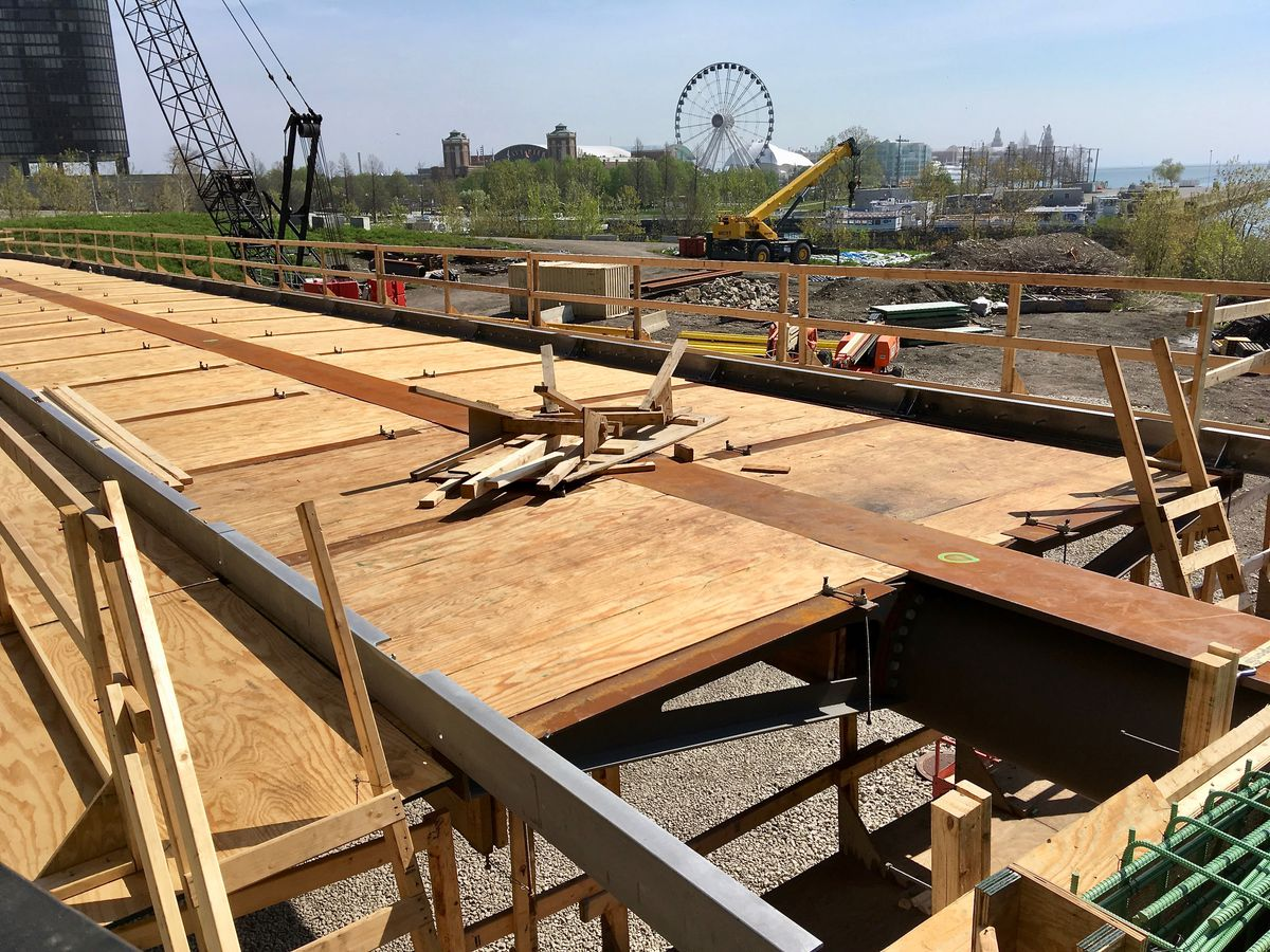 A photo of an under-construction elevated bike trail supported by wood formwork.