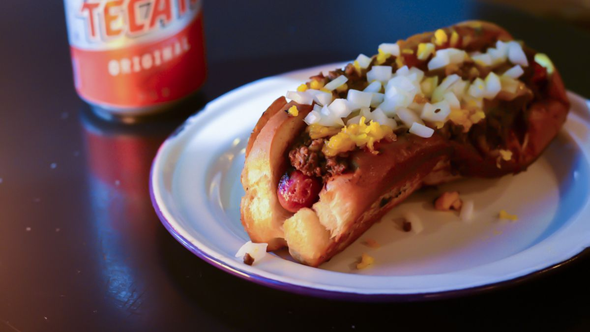 A hot dog covered in chili and chopped white onions sits on a white plate on a dark table, with a can of Tecate beer partially visible in the background
