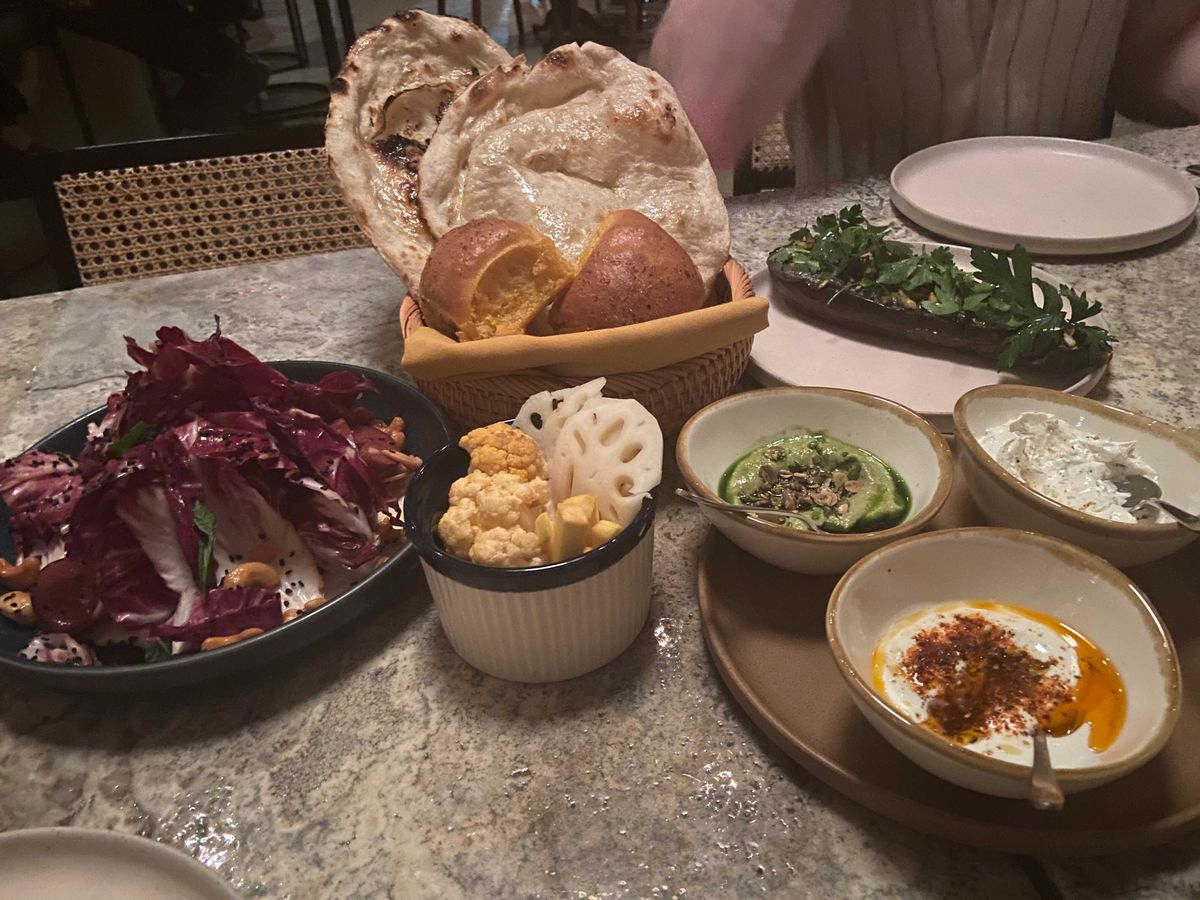 A spread of plates and small bowls featuring mezze such as green chorizo kofta and leafy greens like a radicchio salad served with breads in a basket.