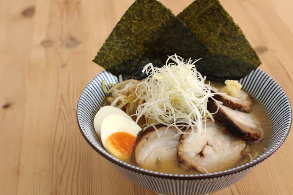 A decorative bowl of broth with slices of pork, hard boiled eggs, shredded cabbage, noodles, and sheets of nori on a wooden countertop