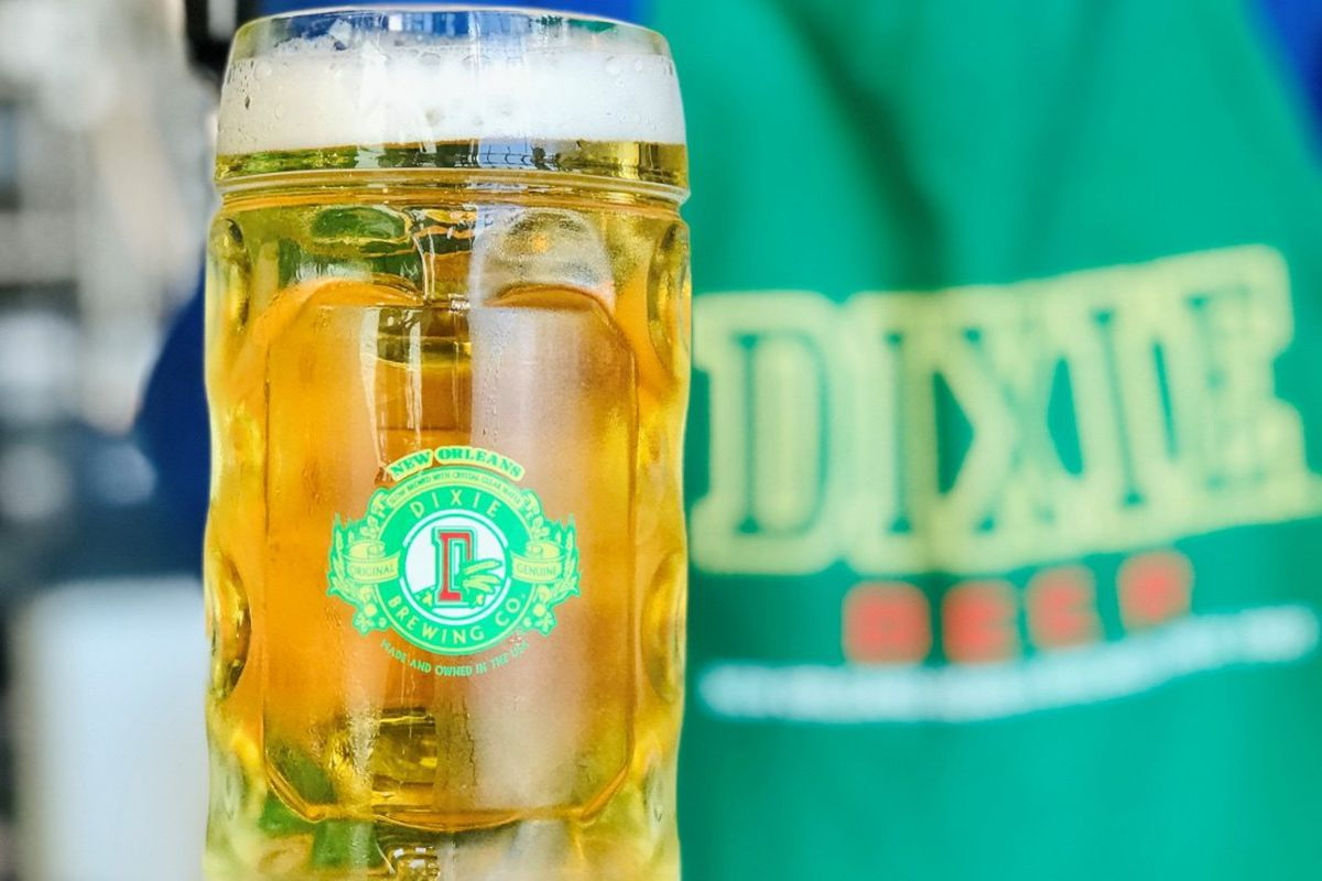 A mug of frothy beer with a Dixie logo is held by a person in a Dixie logo t-shirt