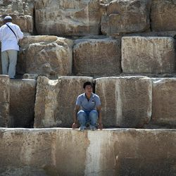 In this Thursday, Sept. 27, 2012 photo, a foreign tourist looks on as he sits during his visit to the historical site of the Giza Pyramids, near Cairo, Egypt. The Egyptian demonstrations against an online film that was produced by a U.S. citizen originally from Egypt and denigrates the Prophet Muhammad were part of a wider explosion of anger in Muslim countries. They happened near the U.S. Embassy, far from the pyramids of Giza on Cairo's outskirts, and a lot further from gated Red Sea resorts, cocoons for the beach-bound vacationer. Yet the online or TV images _ flames, barricades, whooping demonstrators _ are a killjoy for anyone planning a getaway, even though the protests have largely subsided. Tour guides in Egypt say tourist bookings are mostly holding, but they worry about a dropoff early next year, since people tend to plan several months ahead.
