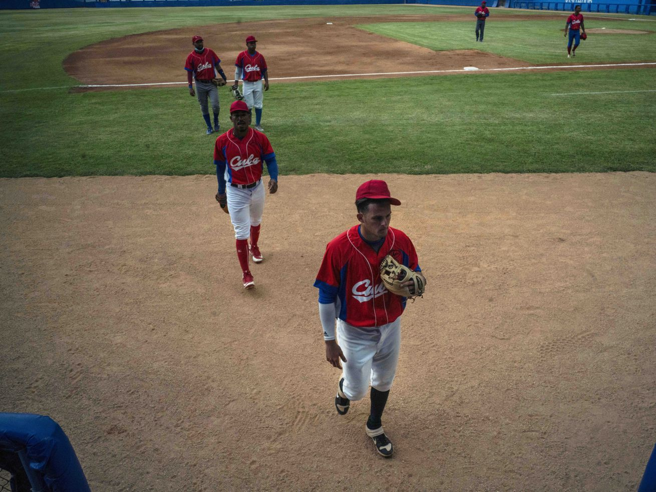 Several Cuban baseball players walk on the field during a break from the training session at the Estadio Latinoamericano in Havana, Cuba.