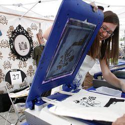 Halen Seevinck prints on a bag using Yudu personal screen printer at the Gallivan Center in Salt Lake City Saturday.