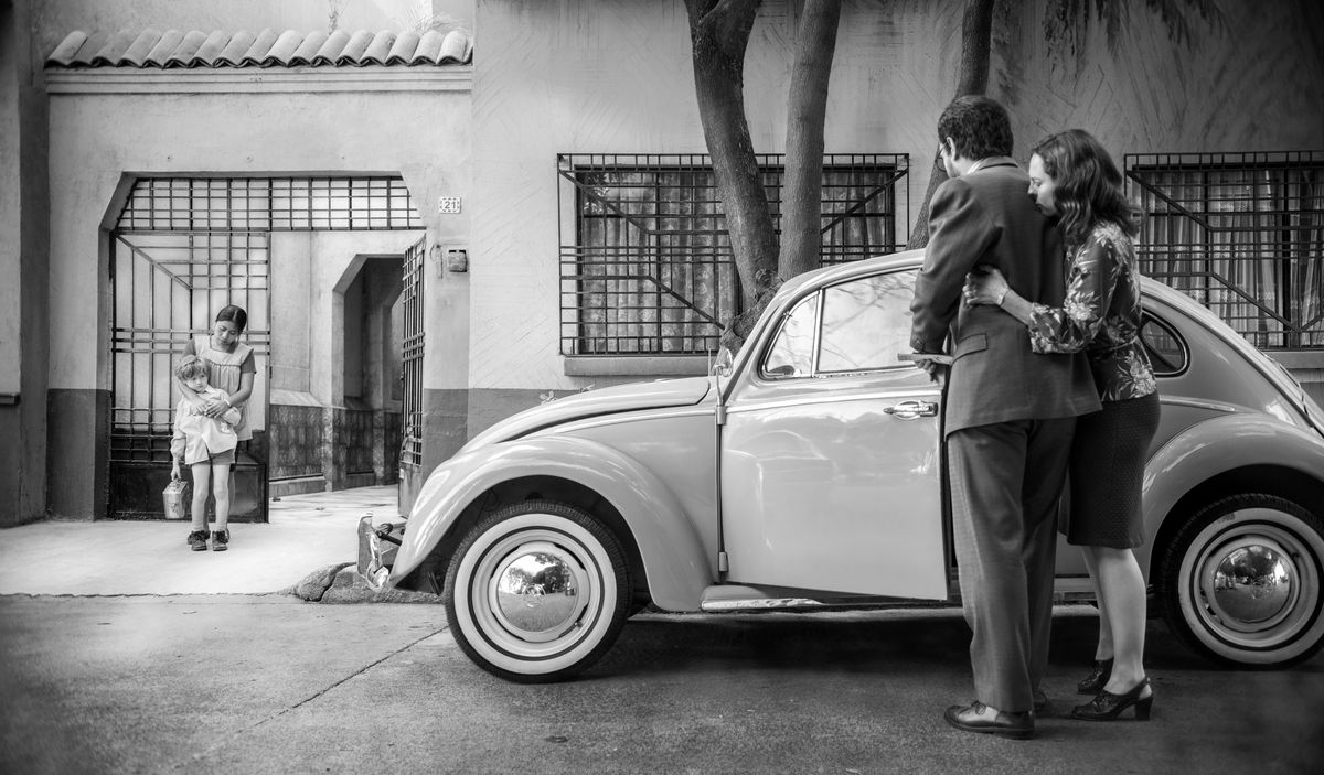 A husband and wife embrace next to their car as one of their children and the family's maid look on from the sidewalk.