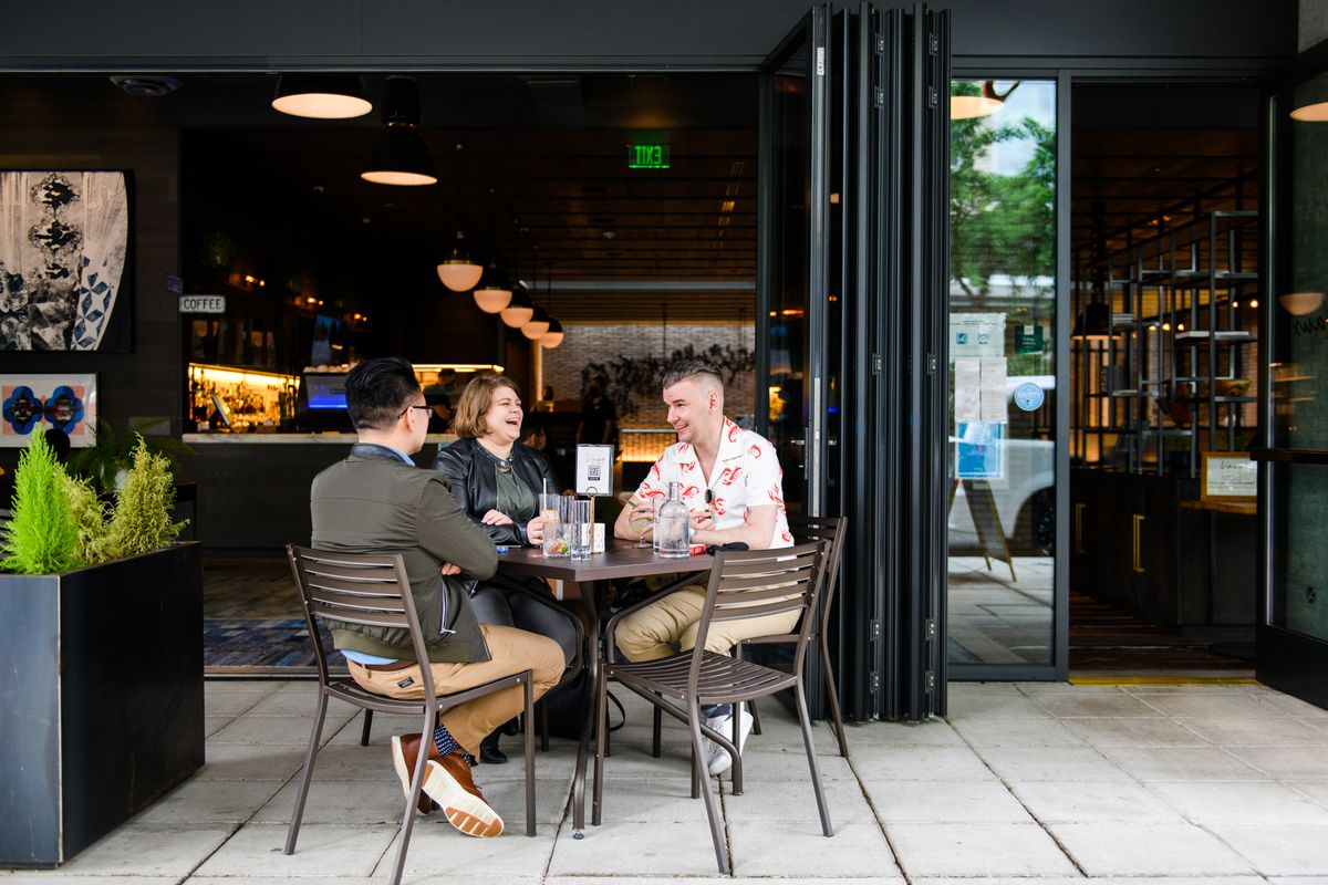 Three diners sit around a table on the patio of Vaux on Sunday, June 21, 2020. A large, garage-door-style window is open into the restaurant.