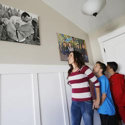 Jenni Thompson look at family photos with her four children Sage, Davin, Cade and Creed at their home in Lehi Nov 23, 2014. Several Thompson family members including her husband have died from cancer.
