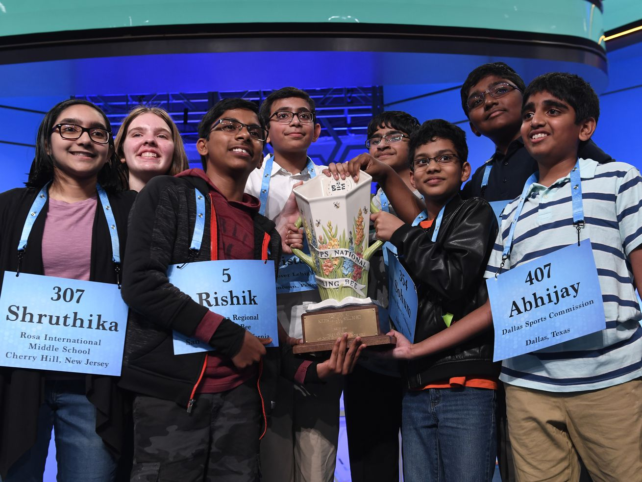 The eight co-champions of the 2019 Scripps National Spelling Bee hold the trophy at the end of the competition in Oxon Hill, Maryland.