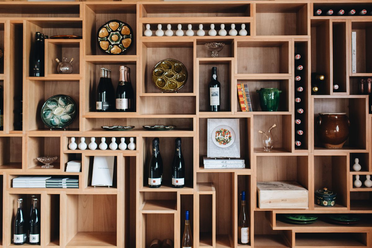 A shelving system with horizontal and vertical slots full of wine bottles, decorative plates, books, and other knickknacks.