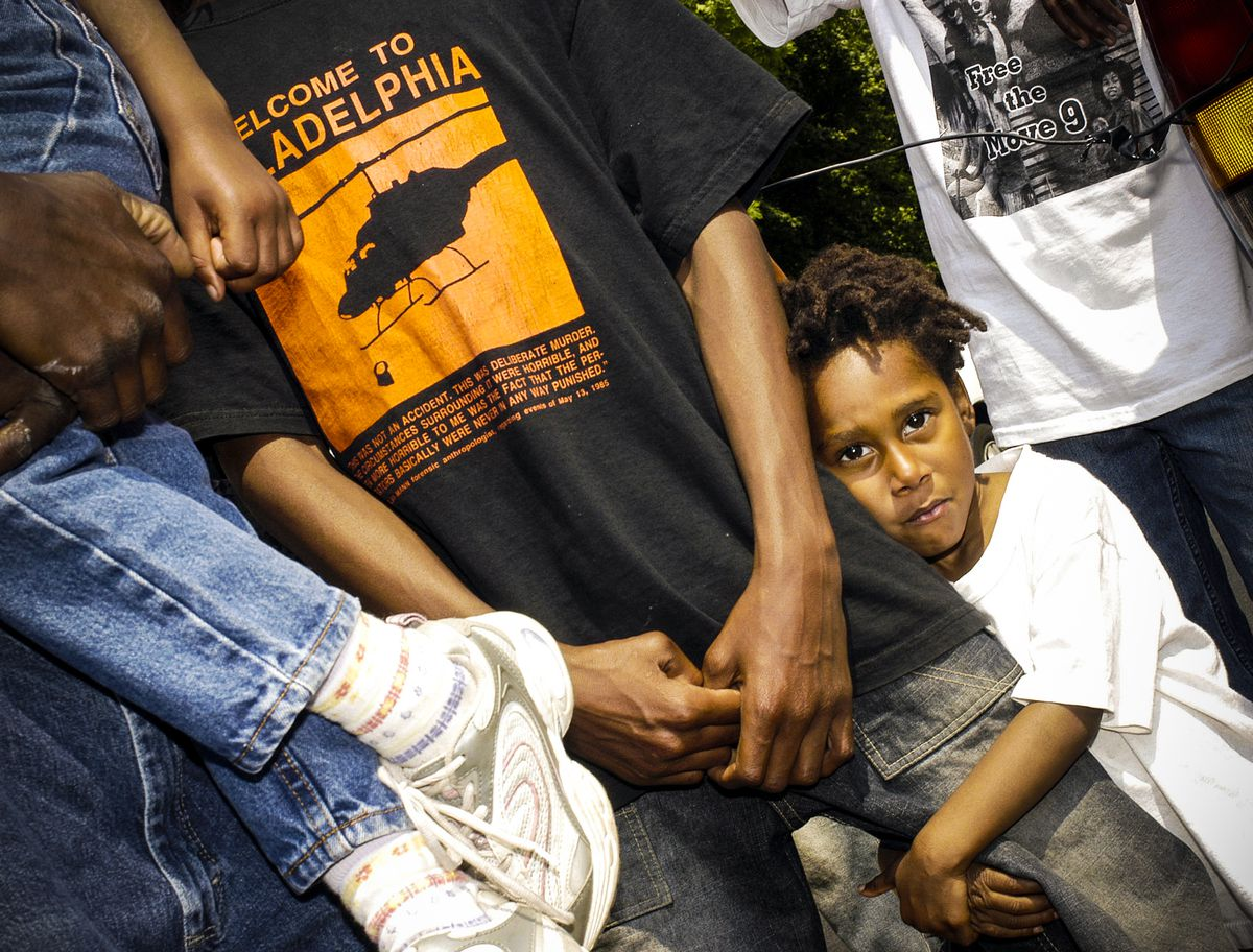 MOVE member's children listen to speechs during a commemorative march for the victims of the 1985 MOVE bombing and fire, on May 14, 2005 in Philadelphia, Pennsylvania.