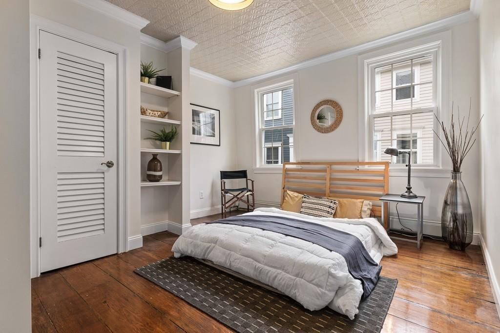 Bedroom with a bed next to a closet and built-in shelves.