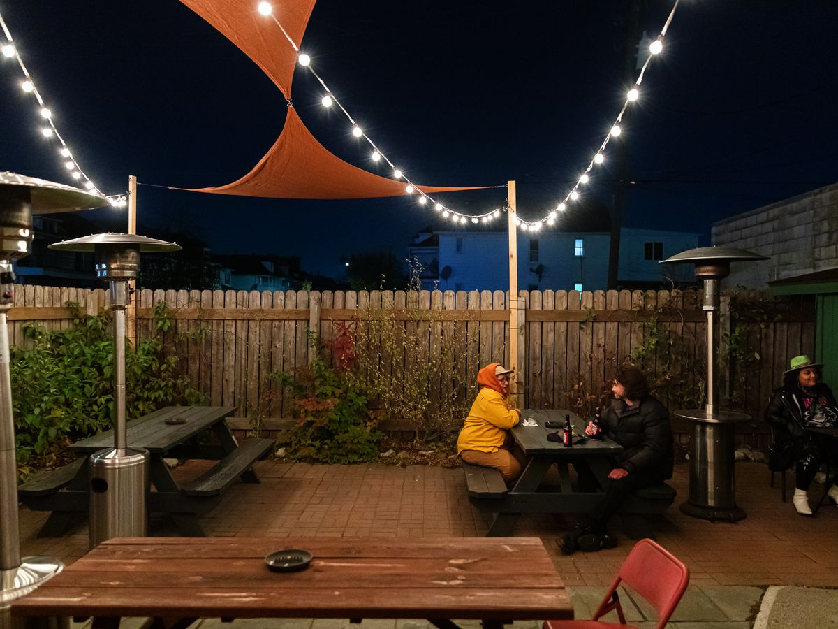 A pair of customers is bundled up outside on an open air patio with heaters at Bumbo's in Hamtramck.