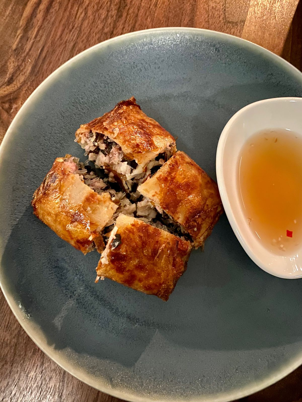 A square shaped deep fried dish that's cut into four pieces and placed on a ceramic plate with a red colored sauce next to it.