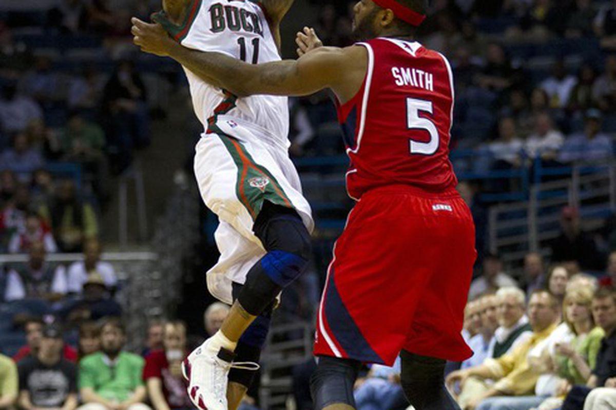 Mar 27, 2012; Milwaukee, WI, USA;  Milwaukee Bucks guard Monta Ellis (11) passes the ball over Atlanta Hawks forward Josh Smith (5) during the third quarter at the Bradley Center.  Mandatory Credit: Jeff Hanisch-US PRESSWIRE