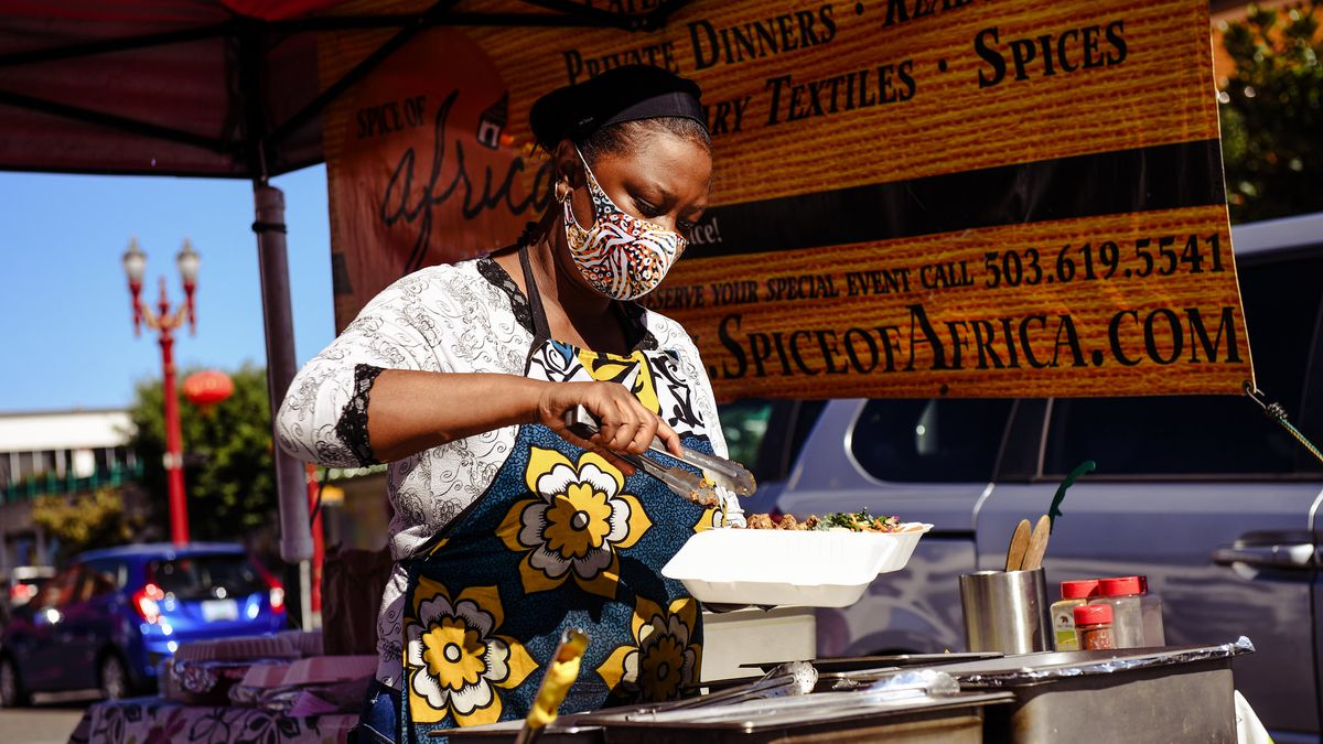 A woman scoops stews into a takeout container while wearing a mask.