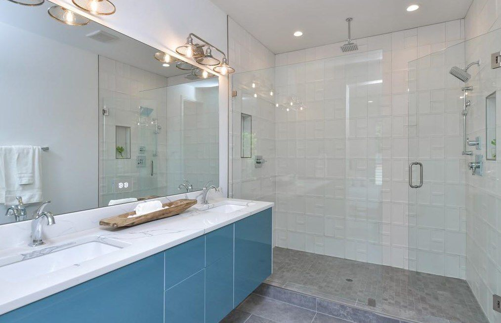 A master bathroom with blue cabinetry and a  huge shower.