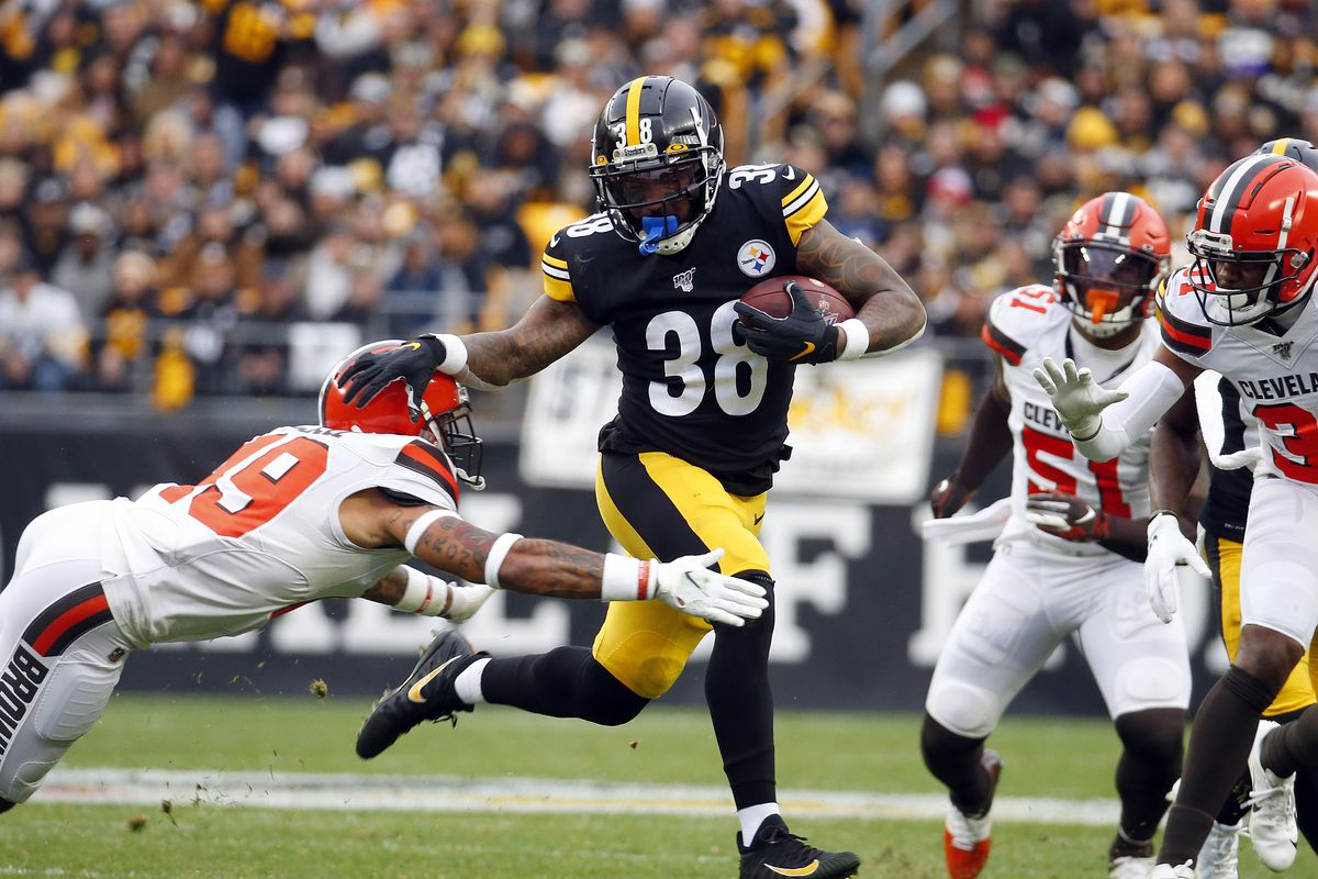Jaylen Samuels of the Pittsburgh Steelers rushes against J.T. Hassell of the Cleveland Browns in the first half on December 1, 2019 at Heinz Field in Pittsburgh, Pennsylvania.