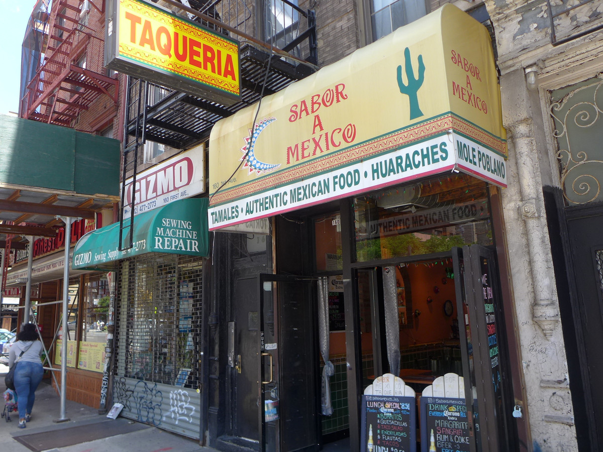 """A small taqueria with a yellow banner that reads """"Sabor A Mexico"""" in red lettering"""