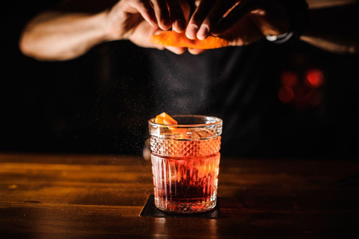 bartender with cocktail and orange peel preparing cocktail at bar