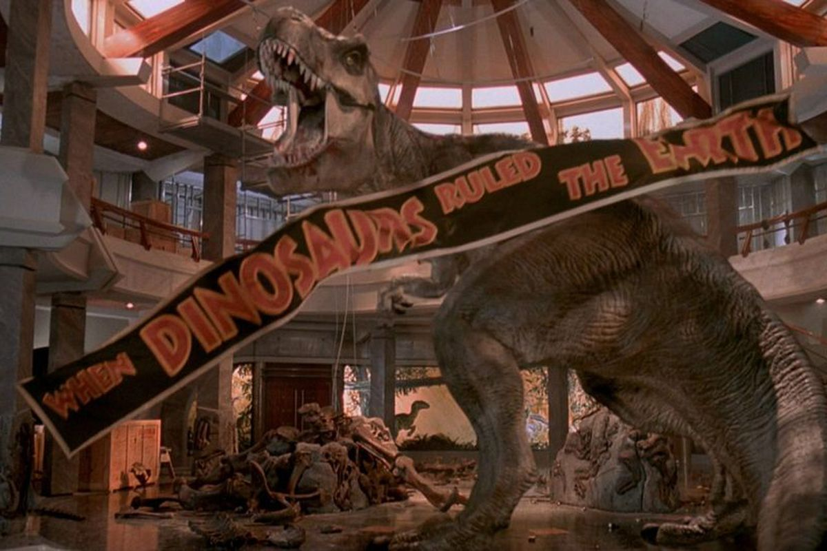A Tyrannosaurus Rex roars in an abandoned atrium as a banner falls around it