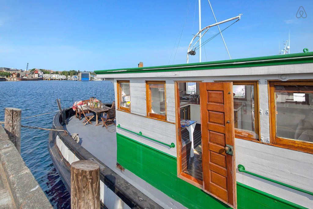 A white, tugboat-style houseboat with green trim