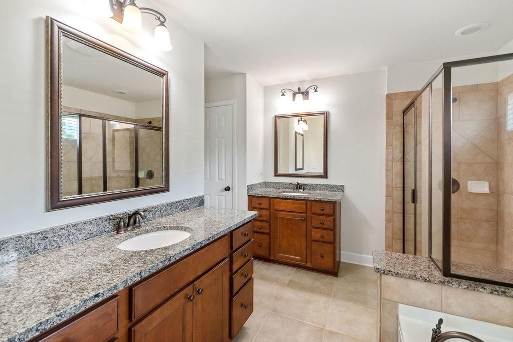 Large bathroom with split vanities, glass shower, and separate soaking tub.