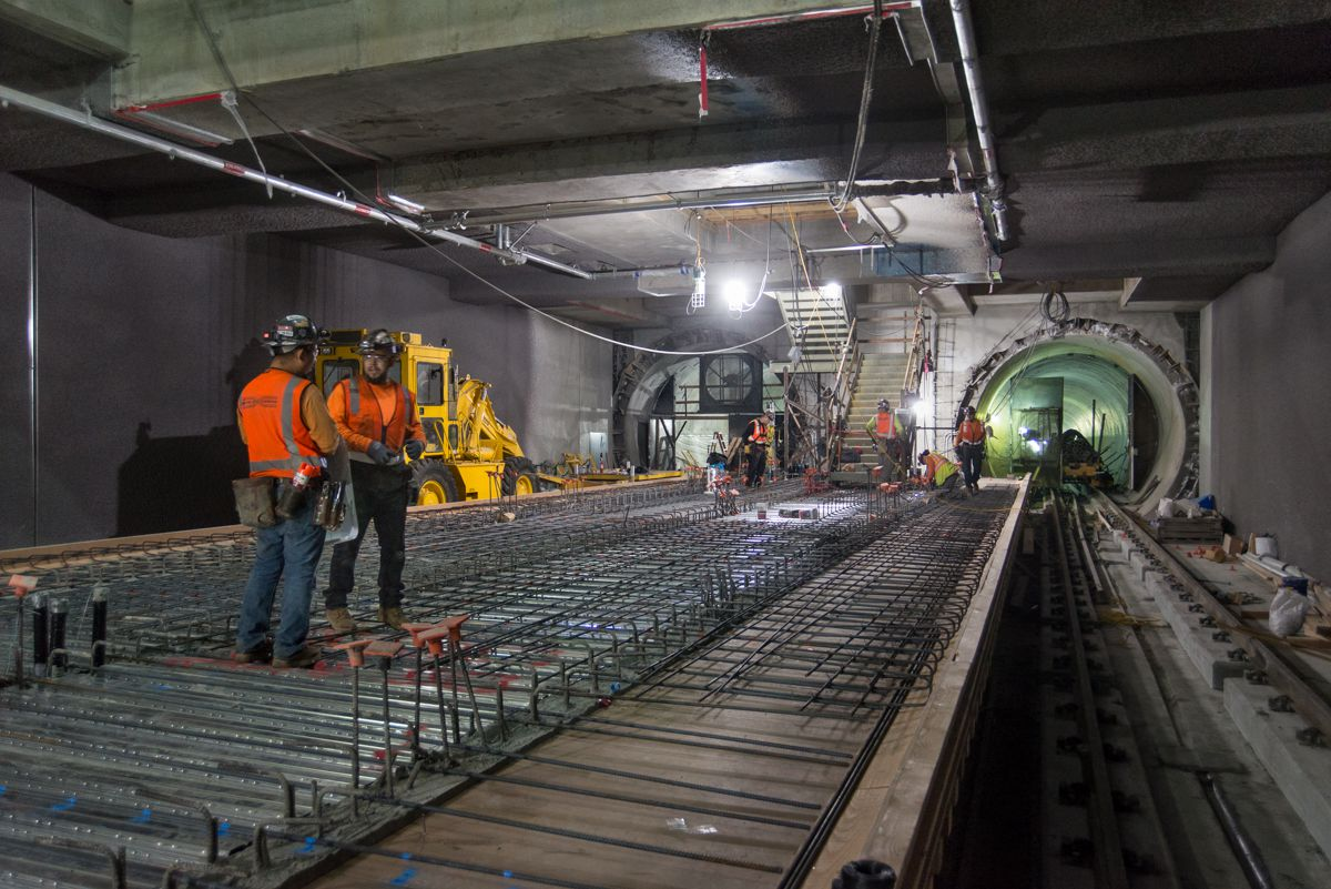 Looking north inside the station box, corrugated sheet steel and rebar are being installed atop sections of station platform foundations, to eventually construct the completed platform.