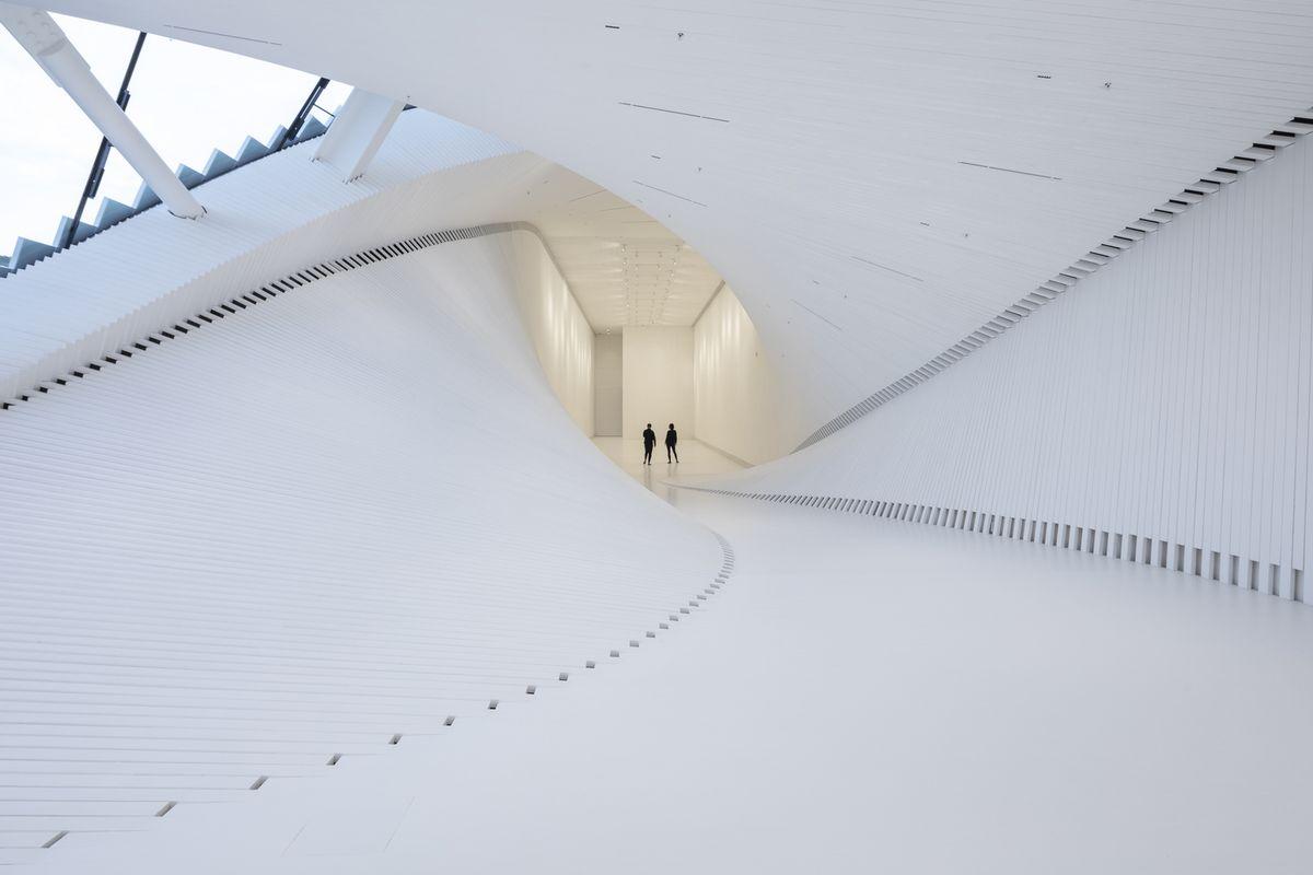 People walking inside white passageway of a covered bridge, where sides curve upward.