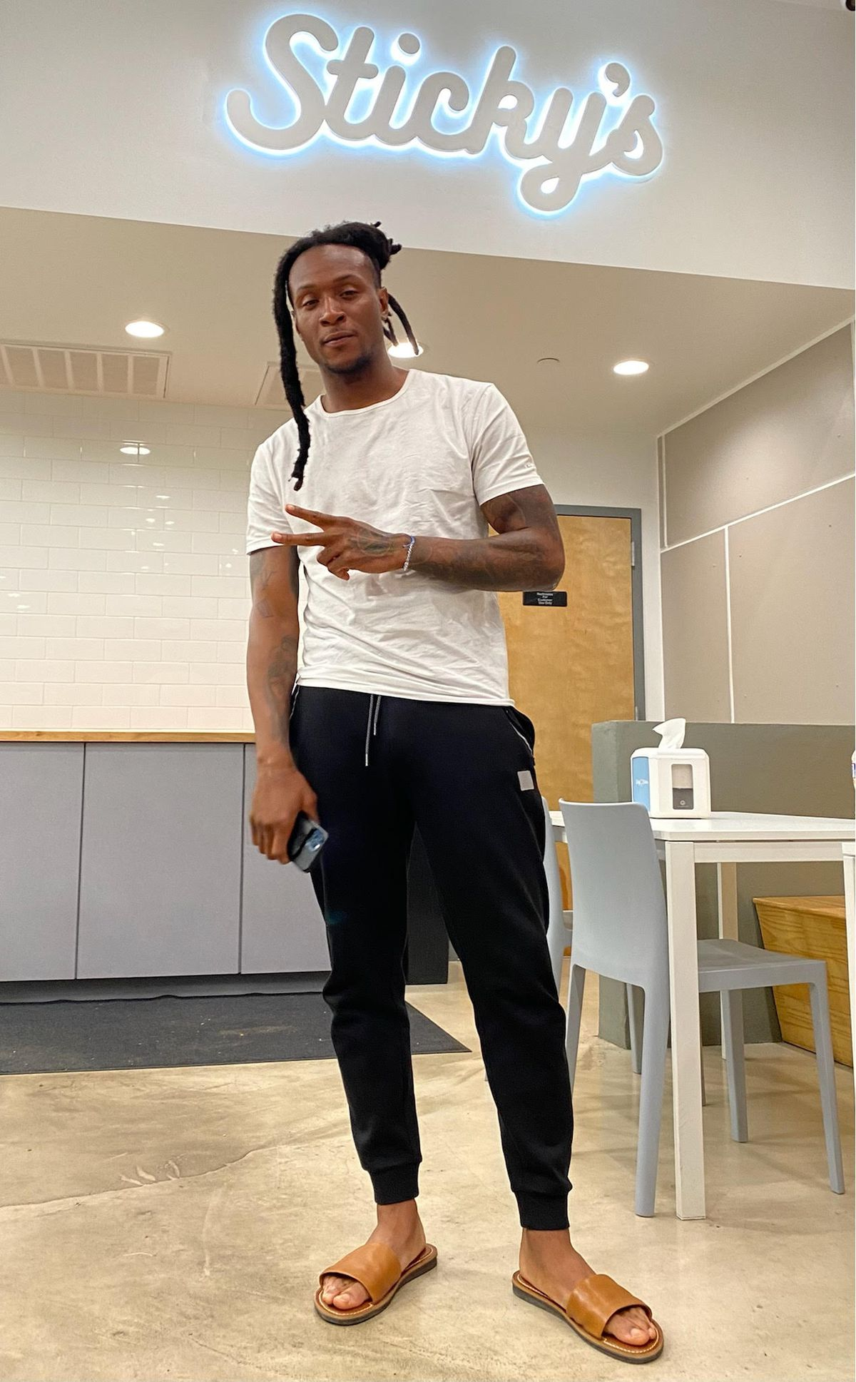"""DeAndre Hopkins, a tall football player in casual clothes, stands before a neon sign in a restaurant which reads """"Sticky's"""""""