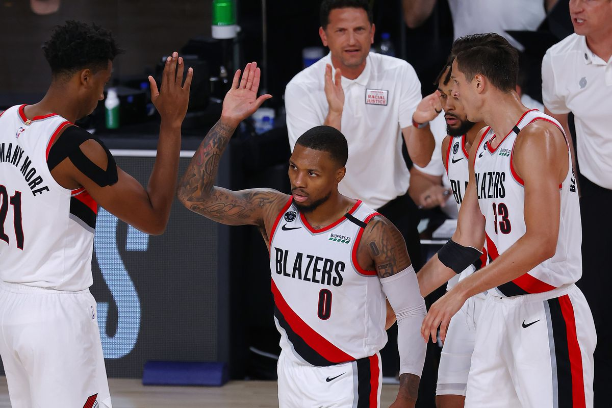 Damian Lillard of the Portland Trail Blazers high fives teammate Hassan Whiteside after a basket against the Boston Celtics at The Arena at ESPN Wide World Of Sports Complex on August 02, 2020 in Lake Buena Vista, Florida.