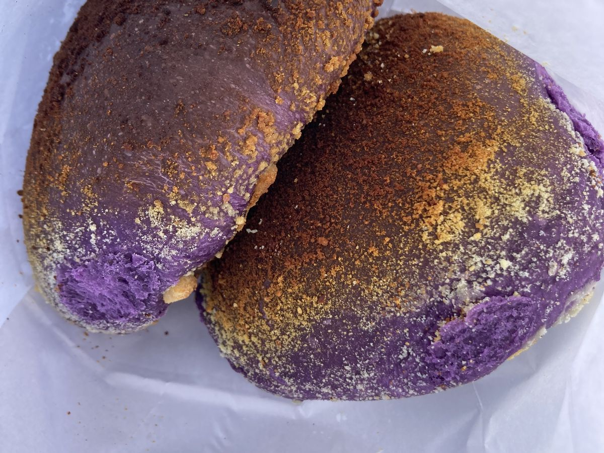 Two filled puffed pastries, with crackly crusts and bright purple filling, wrapped in paper